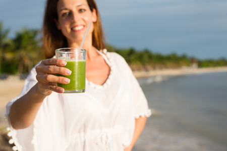 summer diet: Summer diet with green detox smoothie for slim down. Woman holding healthy vegetable drink at tropical beach.