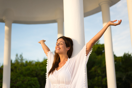 outstretching: Blissful woman enjoying relax and freedom on vacation.  Brunette female raising arms. Happiness and leisure on summer holidays.
