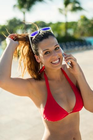 caf4a28f328 #57445555 - 通話のためのスマート フォンを使用してホテル restort に熱帯の夏休みに女性。携帯電話で話している赤いビキニ の幸せな女の子。