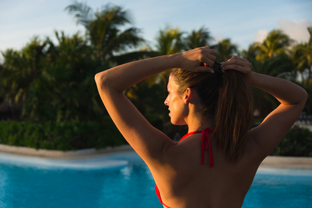 ponytail: Back view of young woman getting ready for sunbathing and enjoying vacation at tropical caribbean resort. Brunette female tying ponytail at poolside. Stock Photo