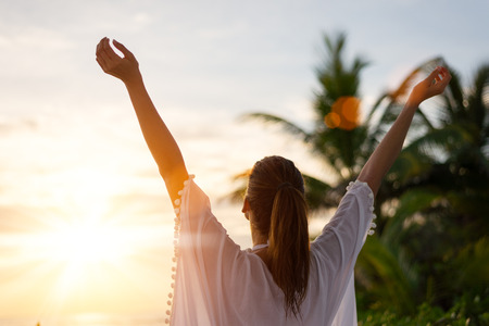 outstretching: Back view of blissful woman at tropical beach enjoying relax, freedom and vacation.  Female raising arms towards the sun on beautiful sunrise. Summer happiness and leisure.
