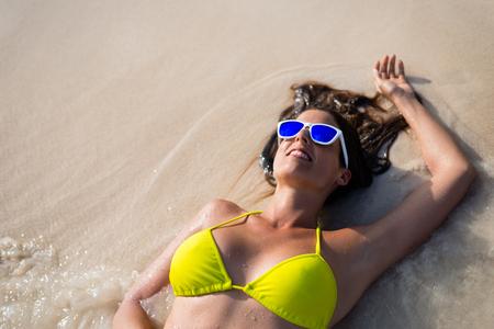 vacaciones en la playa: Mujer feliz relajarse y disfrutar de las vacaciones de verano en la playa. chica morena con gafas de sol que se acuesta en la arena en la orilla del mar. Foto de archivo