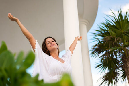 blissful: Blissful serene woman raising arms and enjoying relaxing summer morning vacation at hotel resort.