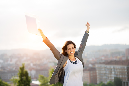 arms up: Young female entrepreneur enjoying business and job success against city and sunset background. Successful businesswoman smiling outdoor.