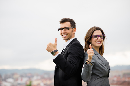 Two modern entrepreneurs partners doing thumbs up gesture for celebrating business success. Successful modern businesspeople outside. Positive elegant man and woman smiling and looking at camera.