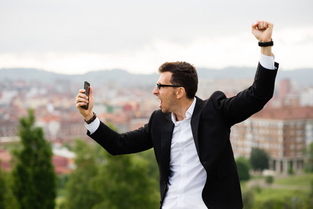 successful man: Successful businessman looking his smartphone. Young casual entrepreneur celebrating business success or good news.