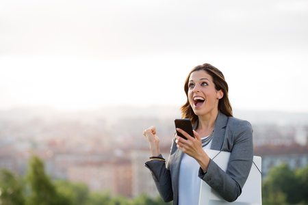 Empresario de sexo femenino joven que celebra buenas noticias y el éxito del negocio. Celebración de la mujer feliz metas de trabajo profesionales. Foto de archivo - 59198282