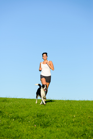 spring training: Fit woman and dog running and exercising outdoor over grass field on summer or spring. Happy female athlete training and exercising with her pet.