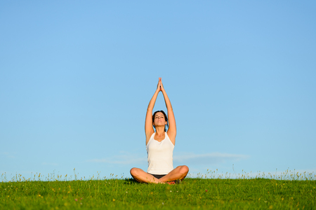 breathing exercise: Woman doing yoga lotus pose and relax breathing exercise outdoor. Healthy fitness lifestyle, wellness and tranquility concept at green grass field against blue copy space sky.