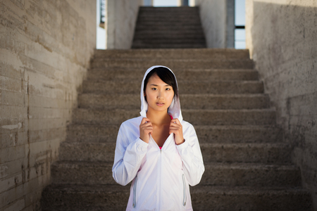 asian lifestyle: Asian female athlete portrait wearing sportswear and hood getting ready for workout. Motivation and sport lifestyle concept. Stock Photo