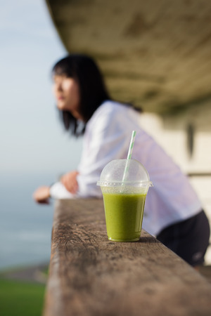 taking a break: Healthy fitness green detox smoothie close up. Woman resting after outdoor workout.