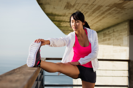 motivated: Asian motivated sporty woman stretching before running or exercising. Healthy lifestyle and sport concept.