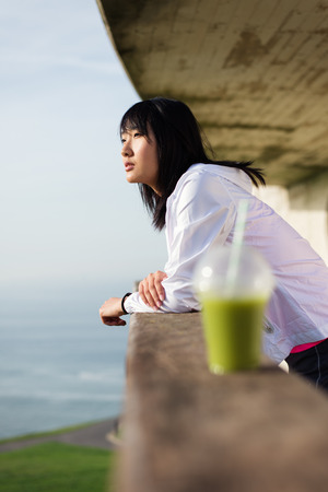 motivated: Sporty motivated woman taking a workout or running rest for drinking detox smoothie towards the sea. Young asian female athlete on urban park training break.