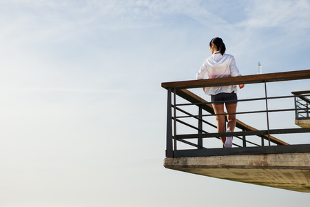 young asian: Back view of asian sporty woman taking a workout or running rest for drinking water towards the sky. Young chinese female athlete on training break. Stock Photo