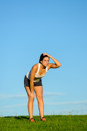 motivated: Tired young woman taking a running workout rest. Motivated female athlete on an exercising break for breathing. Motivation and healthy fitness lifestyle concept.