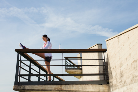 cool down: Asian sporty woman stretching legs for cool down after running or exercising outdoor. Female athlete on fitness training towards the sky. Stock Photo