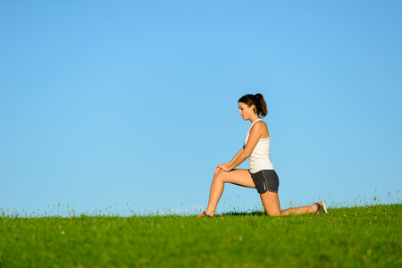 warming up: Sporty woman warming up knee before running or exercising outdoor. Runner joint care for workout.