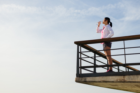 rest: Asian sporty woman taking a workout or running rest for drinking water towards the sky. Young chinese female athlete on training break.