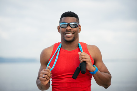 black man: Male successful athlete taking a workout rest after jumping rope outside for warming up before running. Cheerful sporty black man portrait.