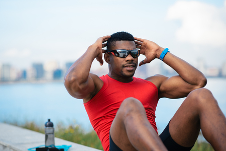 crunches: Man doing crunches. Core outdoor workout. Black athlete exercising.