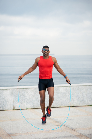 warming up: Cheerful male runner jumping rope for warming up. Black athlete training and doing cardio exercise outside.