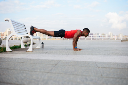 push ups: Male urban athlete doing push ups. Young fit black man working out. Stock Photo