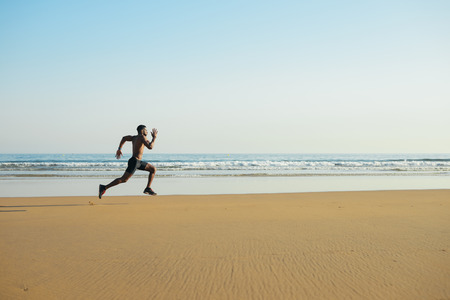 Black fit man running fast by the sea on the beach. Powerful runner training outdoor on summer. Stock Photo