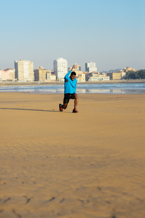 warming up: Runner doing walking lunges exercise for warming up before running workout at the beach.