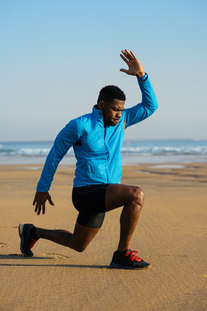 lunges: Runner doing walking lunges exercise for warming up before running workout at the beach.