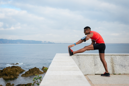 hamstring: Male fit runner stretching towards the sea for warming up before running. Black athlete exercising.