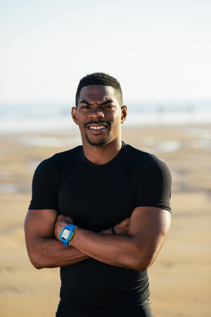 crossing arms: Male athlete portrait during outdoor beach running workout. Successful black fit man crossing arms and smiling.