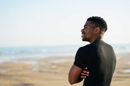 uomo felice: Running and healthy lifestyle success. Cheerful black man taking a workout rest at the beach. Motivation in sport concept.
