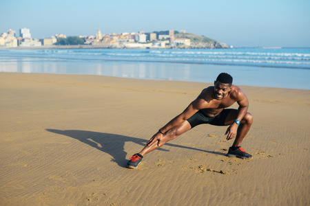 hamstring: Athlete stretching hamstring after running at city beach. Black runner exercising and warming up for outdoor summer workout. Gijon, Asturias, Spain.
