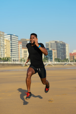 outdoor training: Black fit man running and sprinting at city beach. Athlete training outdoor. Stock Photo