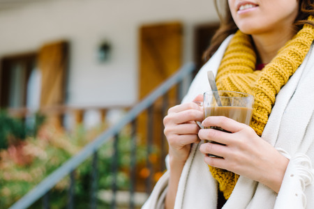 Relaxed woman drinking hot coffee outside on autumn. Tranquility at home concept.