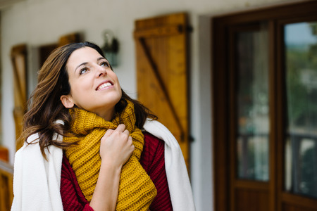 Relaxed woman wearing warm clothes and blanket on cold autumn. Tranquility at home concept.