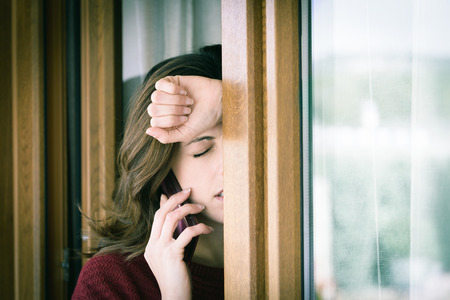 heartbreak: Sad woman on cellphone call looking through the window at grey day. Heartbreak despair, bad news and problems concept.