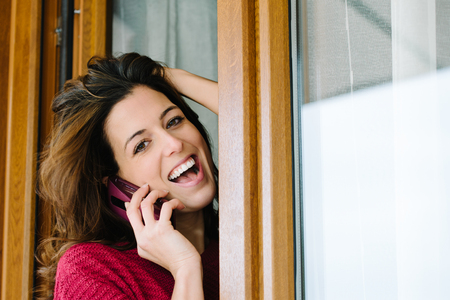 house call: Young happy woman getting good news on cellphone at house window. Blissful girl on fun phone call at home.