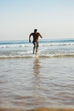 Mensentraining op het strand. Zwarte atleet die de zee voor beenmacht opleiding tegenkomt.