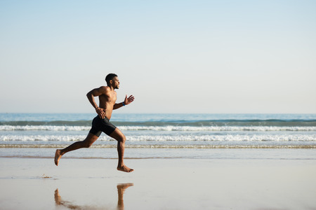 sportsmen: Black fit man running barefoot by the sea on the beach. Powerful runner training outdoor on summer.