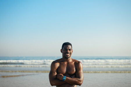 motivated: Black cheerful man posing for portrait at the beach after swimming or running summer workout. Fit motivated athlete smiling and crossing arms towards sea background. Stock Photo