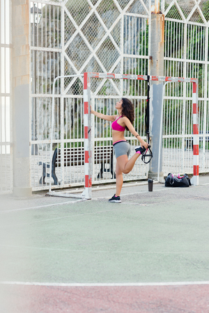 outdoor fitness: Sporty woman stretching legs for warming up before training with trx fitness straps. Outdoor urban workout and fitness lifestyle.