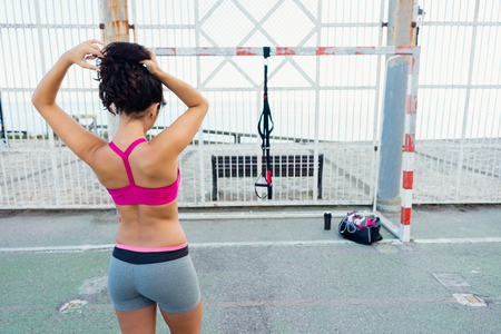 view woman: Back view of sporty young woman getting ready for fitness trx workout with straps. Healthy lifestyle and training outside.