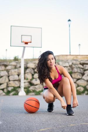 Motivato femminile giocatore cesto allacciatura calzature. Giovane sportiva al campo da basket urbano. Donna sportiva sano allenamento sportivo esterno.