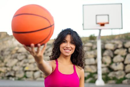 mujer deportista: Joven deportista sosteniendo pelota de baloncesto y sonriendo. Alegre hermosa del deporte de baloncesto mujer morena de juego en la corte urbano exterior.