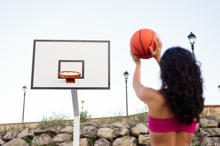 view woman: Back view of young woman playing urban basket sport and throwing the ball to the hoop.