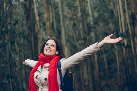 blissful: Blissful woman enjoys freedom and leisure during autumn or winter trip to the forest. Female happy model wearing red scarf raising arms under the trees.