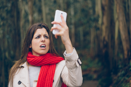 signals: Upset woman looking worried about losing mobile or gps signal coverage on smartphone. Brunette girl in trouble or receiving bad news during autumn trip.