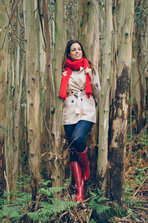 Young woman wearing autumn fashion clothes during trip to the forest. Brunette model in raincoat, red rain boots and knitted scarf.