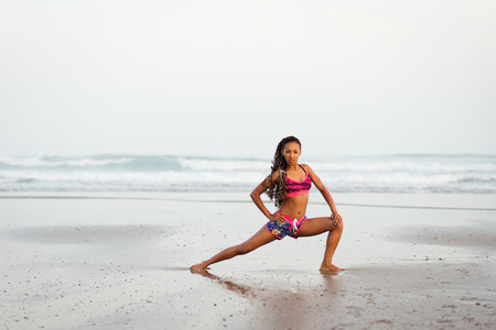 abductor: African woman stretching legs and adductor at the beach. Sporty fit female exercising against the sea. Stock Photo